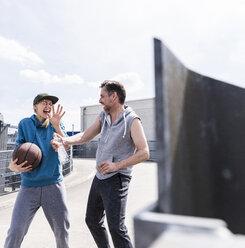 Man and woman playing basketball, splashing water - UUF13642