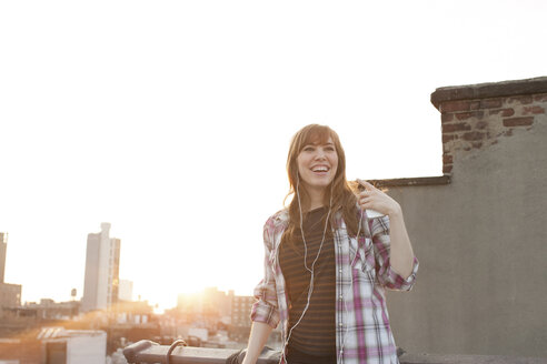 Young woman listening to music on city rooftop - ISF00755