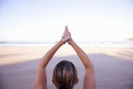 Close up of hands of woman in tree yoga pose on beach - ISF00794