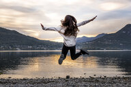 Rear view of young woman jumping mid air by river at dusk, Vercurago, Lombardy, Italy - CUF01868