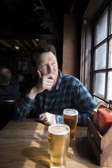 Man having beer looking out of window - CUF01985