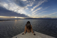 Young woman looking out from pier at sunset, Tarragona, Catalonia, Spain - CUF02015