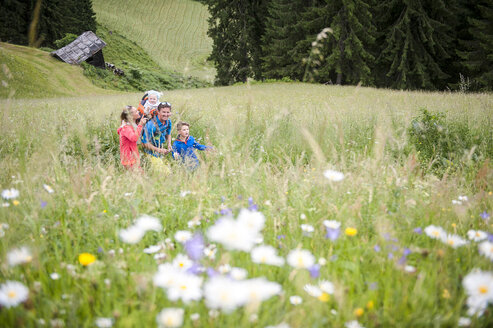 Family hiking in flower meadow - HHF05538