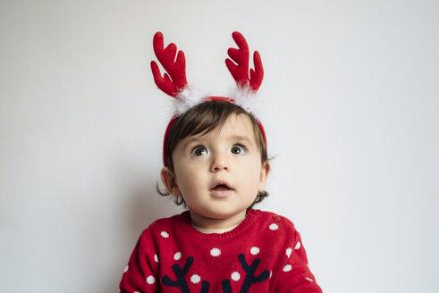 Portrait of astonished baby girl wearing reindeer antlers headband - GEMF01942