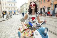 Portrait of young woman wearing pink sunglasses riding scooter on cobbled street, Odessa, Ukraine - CUF02050