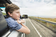 Boy on road trip leaning out of car window - CUF02062