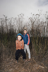 Portrait of two brothers, outdoors, in rural setting, wearing knitted hats, - CUF02098