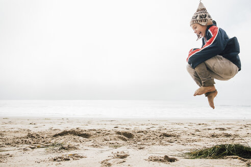 Young boy on beach,jumping, mid air - CUF02107