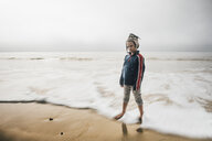 Portrait of boy standing on beach, pensive expression - CUF02110