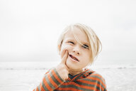 Portrait of young boy on beach, finger on face, making faces - CUF02113