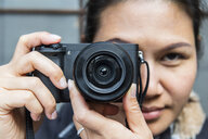 Woman taking pictures with mirrorless digital camera - CUF02128