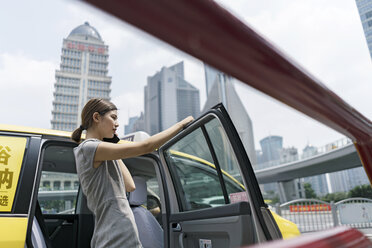 Young businesswoman getting out of yellow cab at Shanghai financial centre, Shanghai, China - CUF02185