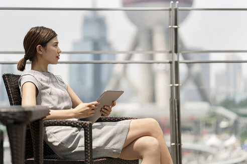 Young businesswoman with digital tablet at sidewalk cafe in Shanghai financial centre, Shanghai, China - CUF02188