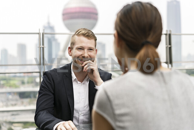 Over shoulder view of young businessman and woman having meeting at sidewalk cafe in Shanghai financial centre, Shanghai, China - CUF02191 - Mick Ryan/Westend61