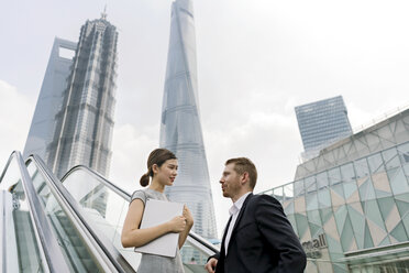 Young businessman and woman moving up escalator in Shanghai financial centre, Shanghai, China - CUF02194