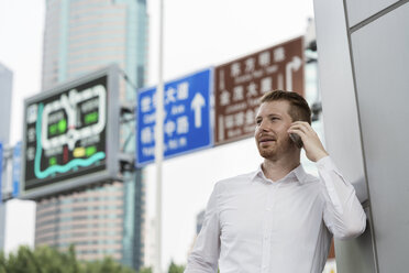 Young businessman making smartphone call in city, Shanghai, China - CUF02197