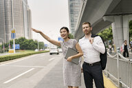 Young businesswoman and man hailing a taxi in city, Shanghai, China - CUF02200