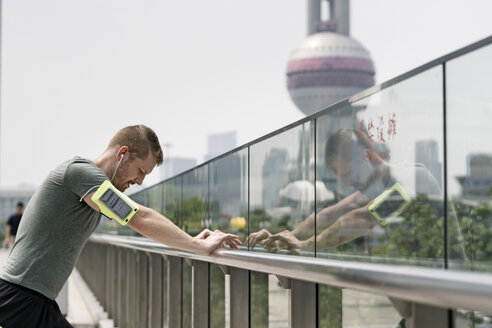 Young male runner leaning against handrail in Shanghai financial centre, Shanghai, China - CUF02203