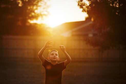 Boy practicing american football in garden reaching for a catch at sunset - CUF02206
