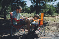 USA, Arizona, Grand Canyon National Park, father and daughter eating outdoors - GEMF01945
