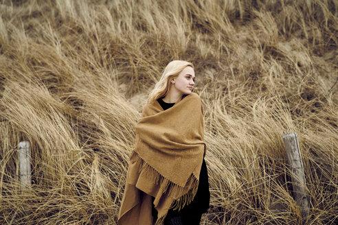 Fashionable young woman wearing light brown cape - MMIF00012