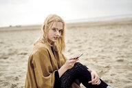 Netherlands, portrait of blond young woman with smartphone sitting on the beach - MMIF00015