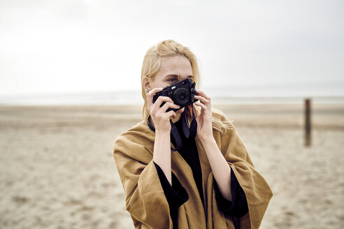 Netherlands, blond young woman taking photo with camera on the beach - MMIF00018