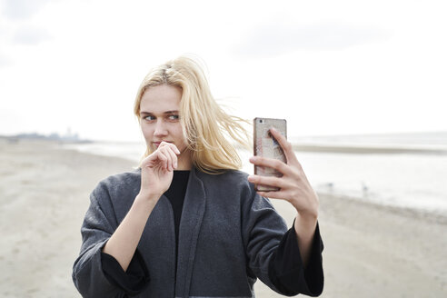 Netherlands, portrait of blond young woman taking selfie with smartphone on the beach - MMIF00021