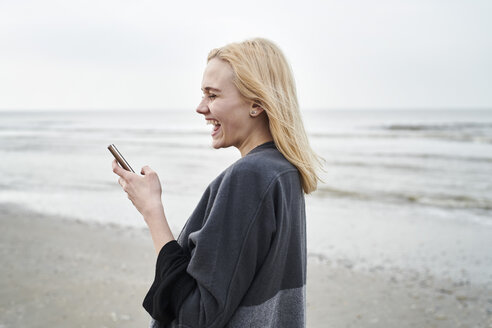 Netherlands, laughing blond young woman using  smartphone on the beach - MMIF00024