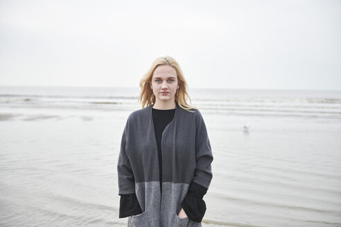 Netherlands, portrait of blond young woman on the beach - MMIF00027