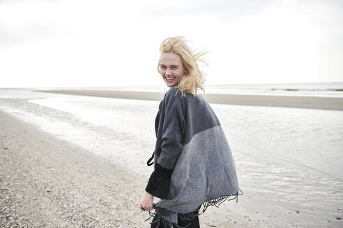 Netherlands, portrait of laughing blond young woman on the beach - MMIF00030