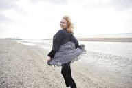 Netherlands, portrait of laughing blond young woman on the beach - MMIF00033
