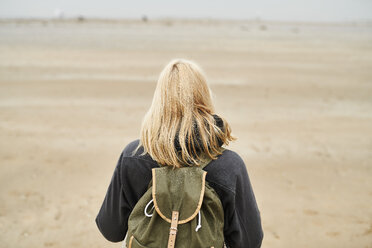 Back view of blond young woman with backpack on the beach - MMIF00039