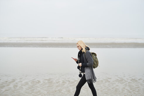 Netherlands, young woman with backpack walking on the beach looking at cell phone - MMIF00042