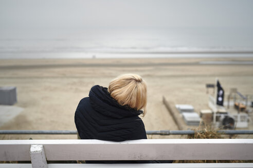 Back view of blond young woman sitting on bench looking to beach and sea in winter - MMIF00048