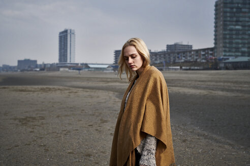 Netherlands, Zandvoort, portrait of  blond young woman on the beach wearing light brown cape - MMIF00051