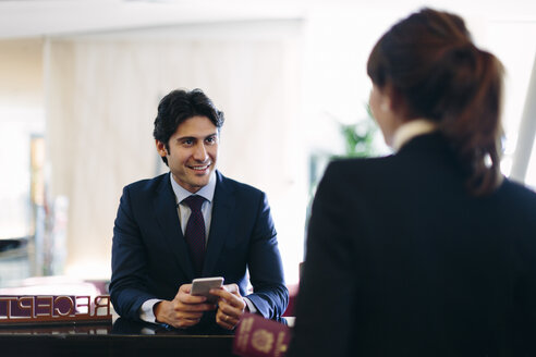 Businessman checking in at hotel reception - CUF02435