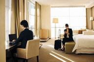 Businessman and businesswoman working in hotel bedroom - CUF02450