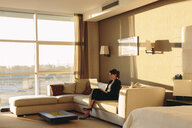 Businesswoman using laptop in lounge area of hotel bedroom - CUF02453
