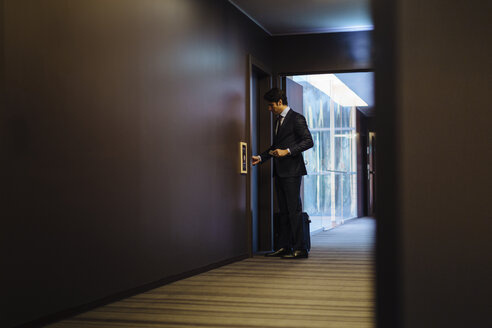 Businessman with wheeled luggage entering hotel bedroom - CUF02462