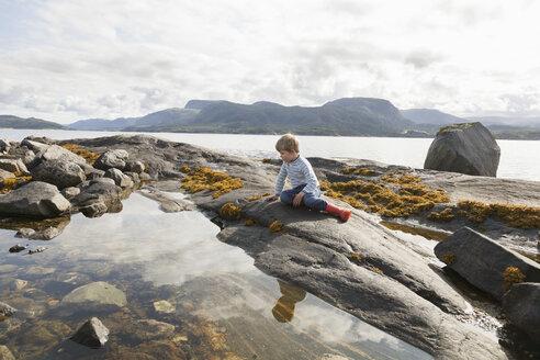 Boy looking at fjord rockpool, Aure, More og Romsdal, Norway - CUF02561