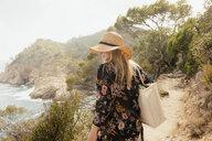Woman walking along coastal pathway, rear view, Tossa de mar, Catalonia, Spain - CUF02576