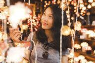 Tourist admiring decorative lights in bazaar, Bangkok, Thailand - CUF02582