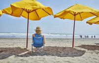 Rear view of female tourist sitting under beach umbrella, Camana, Arequipa, Peru - CUF02597