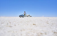 False perspective image of boy and toy truck on salt flats, standing taller than recreational vehicle in background, Salar de Uyuni, Uyuni, Oruro, Bolivia, South America - CUF02606