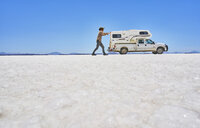 False perspective image of boy on salt flats, pretending to push recreational vehicle, vehicle in background, Salar de Uyuni, Uyuni, Oruro, Bolivia, South America - CUF02609