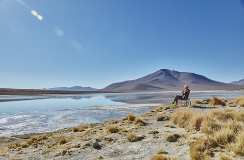 Woman sitting in camping chair, looking at view, Salar de Chalviri, Chalviri, Oruro, Bolivia, South America - CUF02624