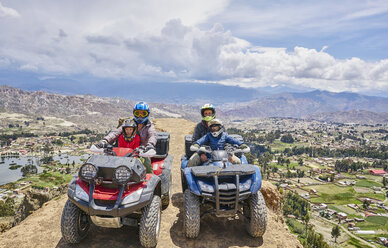 Family on top of mountain, using quad bikes, La Paz, Bolivia, South America - CUF02639