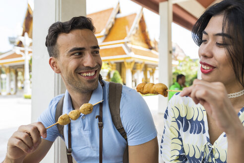 Young tourist couple eating skewered street food outside temple, Bangkok, Thailand - CUF02657