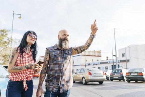 Mature hipster couple hailing a cab, Valencia, Spain - CUF02702